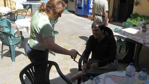 Na foto aparece uma mulher em pé e um peregrino sentado à sua frente. Ela segura uma serra fingindo cortar o pé do peregrino, brincando que não há solução para o pé dele.