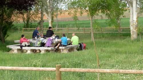 A foto mostra alguns peregrinos descansando sentados em bancos de concreto que ficam em volta de uma mesa também de concreto. Esta é a única área de descanso entre El Burgo Ranero e Reliegos.