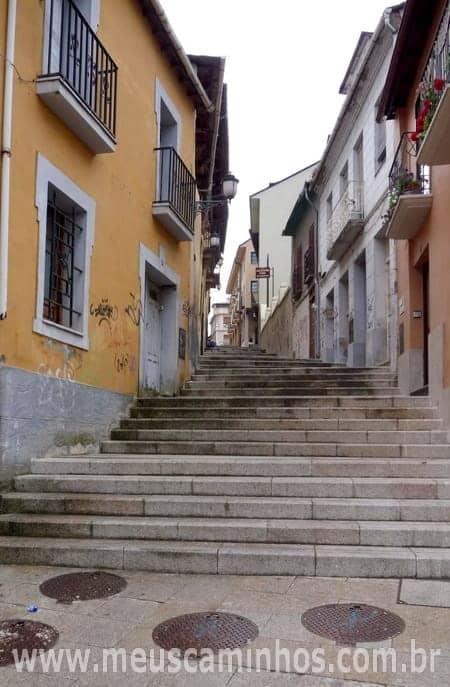 Foto da escadaria logo depois da Praça da Virgem, em Ponferrada, vista de baixo. Ao lado da escadarias há várias casas.